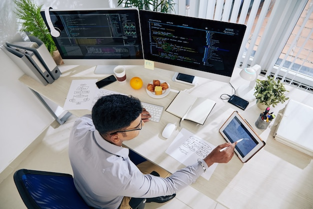 大きなプロジェクトのプログラミングコードの作業を計画するときにタブレットコンピューターでカレンダーをチェックするソフトウェア開発者