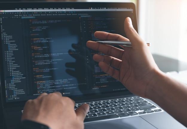 Software developer coding javascript on laptop computer