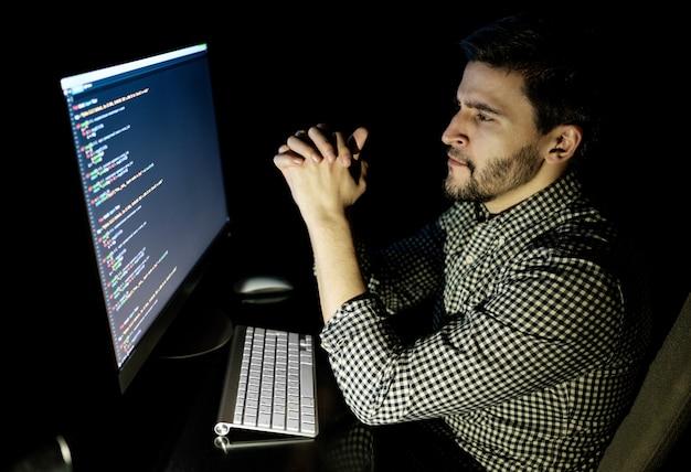 Компьютер разработчика программного обеспечения в темном домашнем офисе