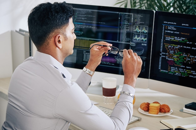 一日中プログラミングコードに取り組んだ後、目を休めるために眼鏡を外すソフトウェア開発者