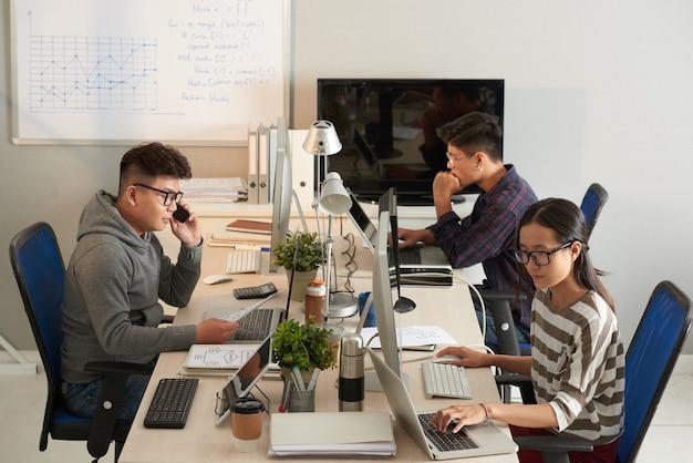 大きなオフィスのテーブルでコンピューターに取り組んでいるソフトウェアテスト部門