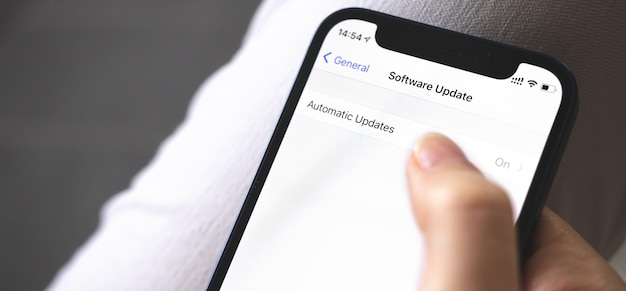 Software update screen on mobile phone close-up, automatic update button, banner photo