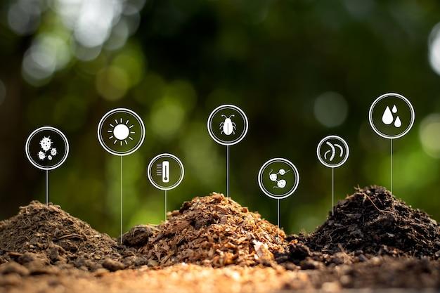 緑豊かな自然の真ん中に、土、肥料、おがくずが積み上げられています。