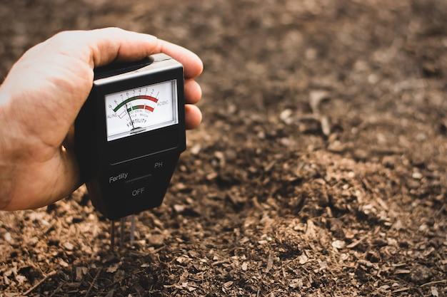 植栽用ロームに土壌計を使用し、土壌の酸性度を測定します。
