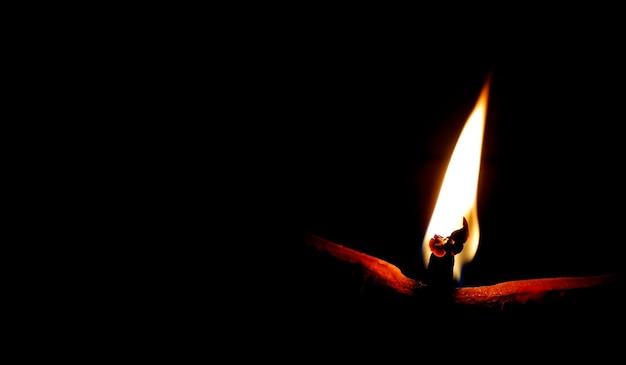 Земляной или глиняный светильник, излучающий свет в темноте. концепция устранения тьмы с помощью пламени.