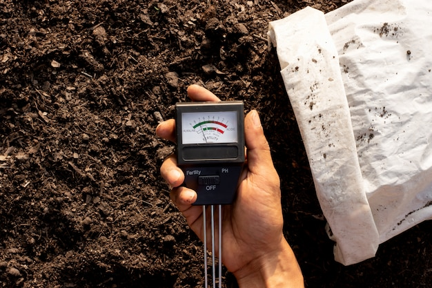 Soil quality meter in the hands of a man who is checking the soil for planting.