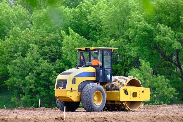 Почвенный каток, дорожный каток, создание нового шоссе. тяжелая промышленная машина, работающая на строительстве новой дороги