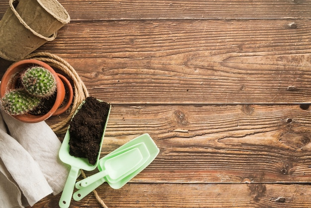 Soil; stacked of potted plant and napkin on wooden desk