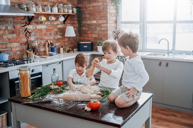 캐주얼한 옷을 입은 더럽고 어린 아이들은 화창한 날 현대식 주방에서 요리를 배우고 밀가루를 가지고 노는 법을 배웁니다.
