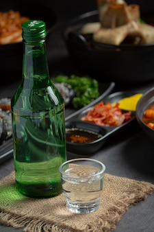 Soju bottles and korean side dishes on the menu