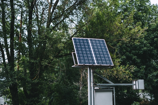 Панель солнечных батарей в городском парке возле зеленых деревьев.