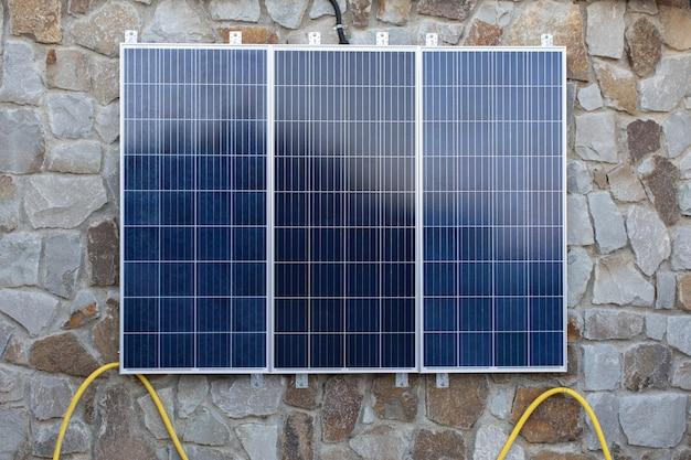 집 벽에 설치된 태양 전지 시스템. 전기를 축적하는 3단 패널. 측면보기. 개념 환경 친화적이고 경제적인 가정 전기화, 녹색 에너지원.