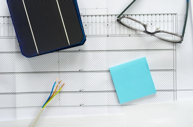 Solar cell, eyeglasses, post it and cable in  a conceptual image for thinking of swithching to solar power. top view over blueprints with copy space.