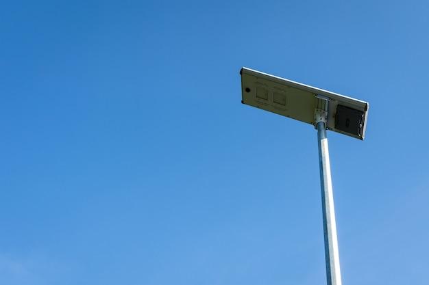 푸른 하늘 배경에 태양 전지 패널 led 조명 기둥.