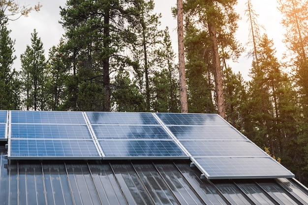 Solar cell panel on roof house with sunlight shining in pine forest