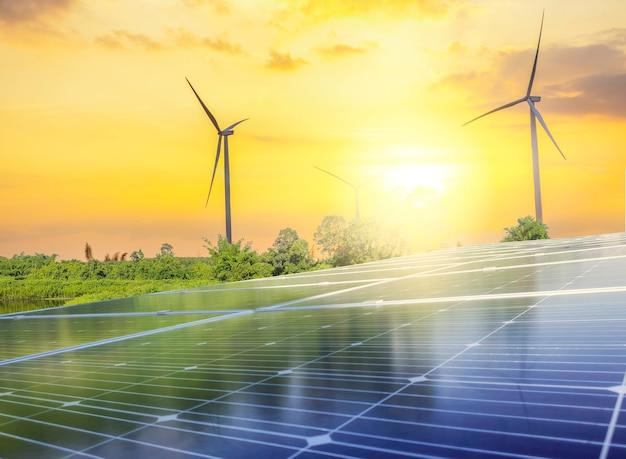 Панели солнечных батарей и ветряные турбины в закатном небе для альтернативного источника энергии