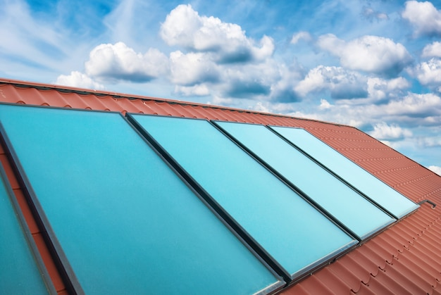 구름과 푸른 하늘 위에 빨간 집 지붕에 태양 전지