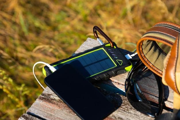 Устройство батареи солнечной энергии, внешний аккумулятор и телефон на деревянном столе с рюкзаком. зарядите свой смартфон от солнечной батареи. выборочный фокус