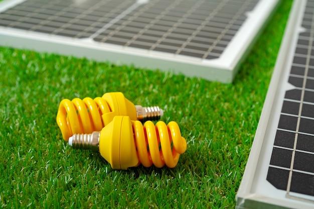 太陽エネルギーパネルと電球のグリーンエネルギー