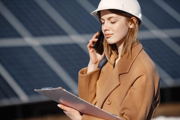 태양 에너지 스테이션. 젊은 여성 엔지니어 공장에서 작동합니다. 그녀는 전화로 이야기하고 사업을하고 있습니다. 서류와 함께 헬멧에 여자입니다.