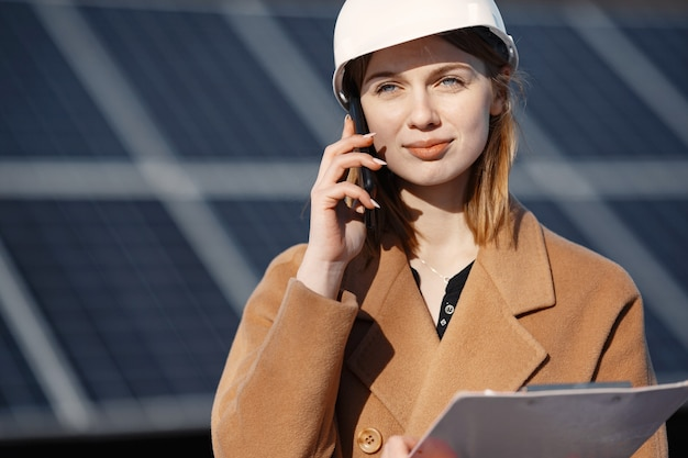 Solar energy station. young female engineer work at plant. she is talking by phone anddoing business. woman in helmet with papers.