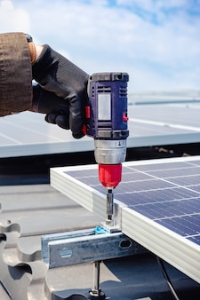 Solar engineer male hand working with drill installing solar panel on house roof against blue sky. solar energy power. sun electricity technology. stock photo solar panels.