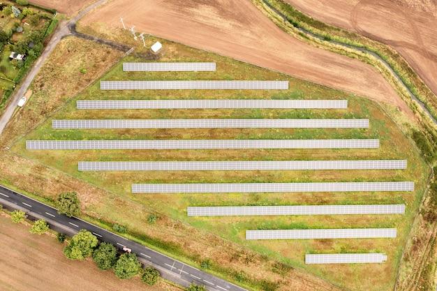 Солнечная ферма на поле, много солнечных батарей в ряд. альтернативный источник энергии