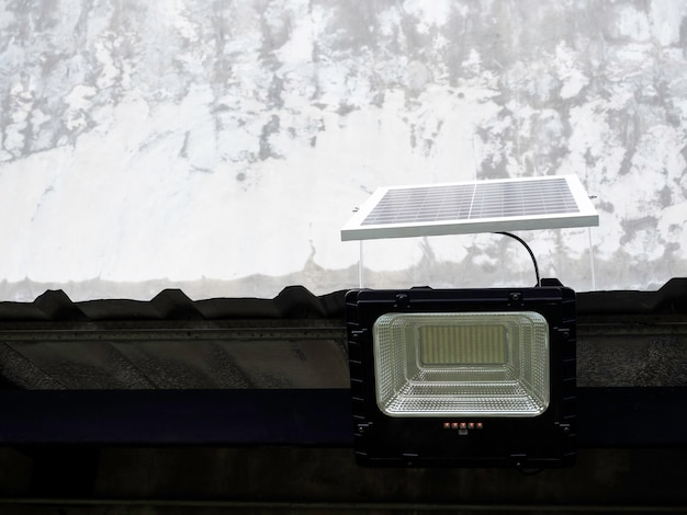 Solar light mounted on a roof on concrete building background with copy space. street lamp with solar panel.