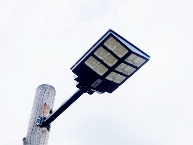 Solar light mounted on a wooden pole on blue sky background. street lamp with solar panel, view from under.