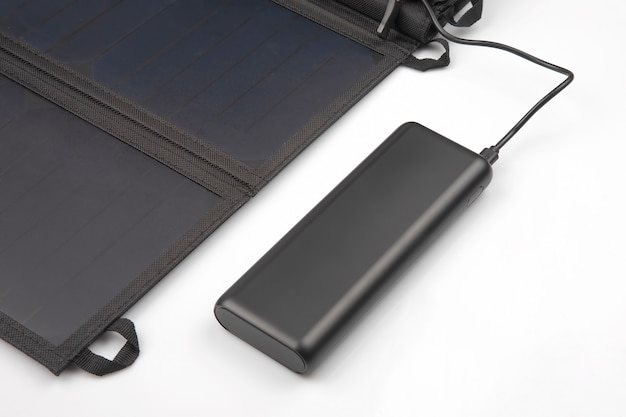 The solar panel charges the power bank battery for the smartphone on a white