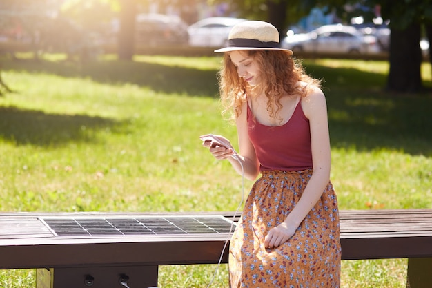 Solar panel for charging, built into bench in park. foxy haired woman in casual clothes useing alternative electricity. modern technology, ecology, free alternative energy for all people concept.