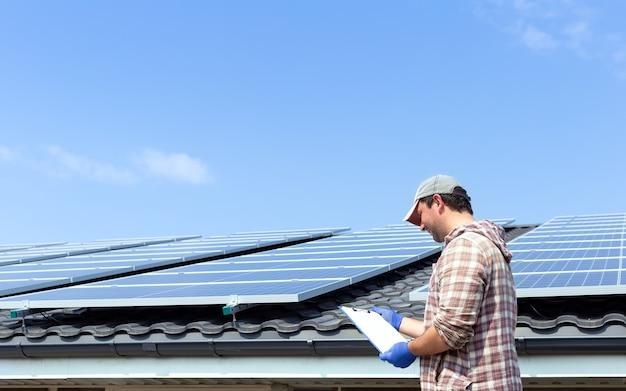 Энергия солнечных панелей. человек инженер-электрик работает, проверяя документы на солнечной станции против крыши дома и голубого неба. развитие технологий альтернативной энергии солнца.