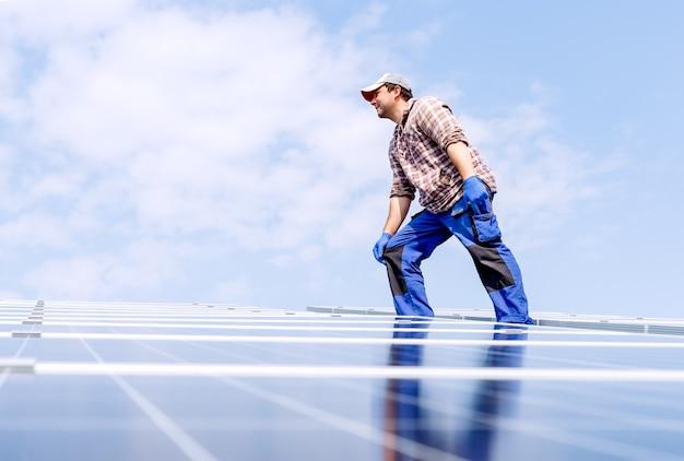 Энергия солнечных панелей. человек инженер-электрик работает в солнечной станции на крыше против голубого неба в солнечный день. развитие технологий альтернативной энергии солнца. экологическая концепция.