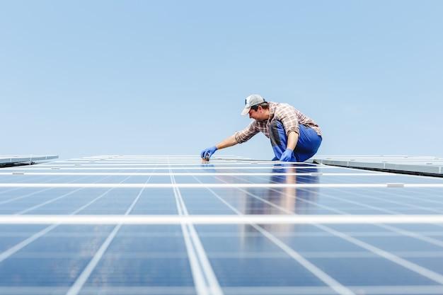 Энергия солнечных панелей. человек инженер-электрик работает в солнечной станции на крыше против голубого неба, используя оборудование. развитие технологий альтернативной энергии солнца. экологическая концепция.