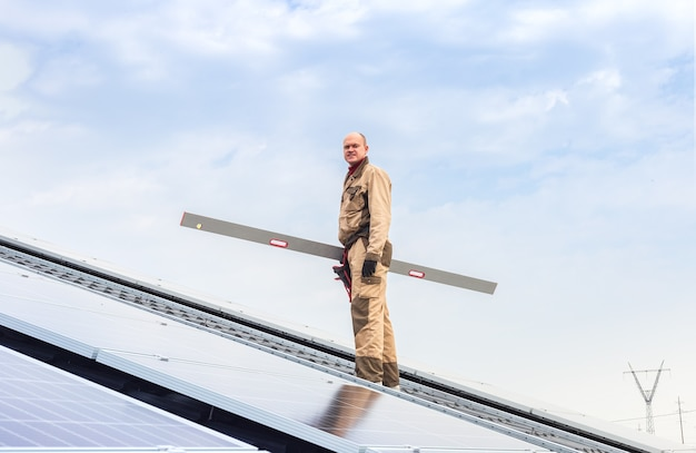Энергия солнечных панелей. человек инженер-электрик работает в солнечной станции на крыше против голубого неба, используя проверку уровня оборудования. развитие технологий альтернативной энергии солнца. экологическая концепция.