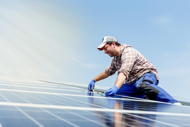 Энергия солнечных панелей. человек инженер-электрик работает в солнечной станции на крыше против голубого неба с солнечными лучами в солнечный день. развитие технологий альтернативной энергии солнца. экологическая концепция.