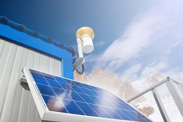 Панель солнечных батарей в горном озере на фоне голубого неба. концепция альтернативной энергии.