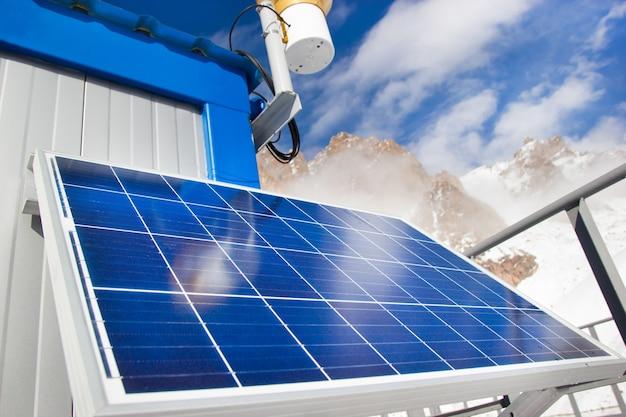 青空の背景に山の湖のソーラーパネル。代替エネルギーの概念。