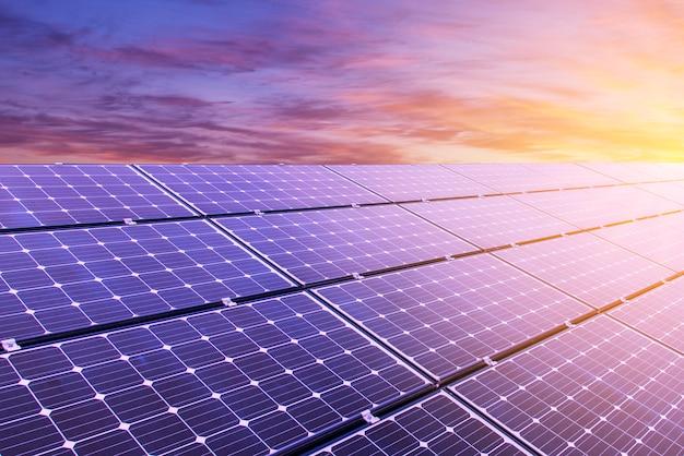 Панель солнечных батарей на фоне красочных неба и солнечного света