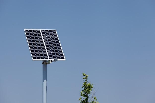 Панель солнечных батарей или солнечная батарея на полюсе на фоне голубого неба. альтернативный источник энергии, дополнительный аккумулятор.