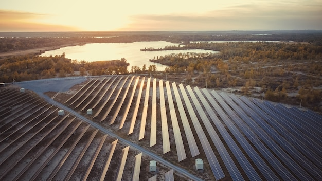 Солнечная панель с отражением солнца и реки на фоне экосистемы
