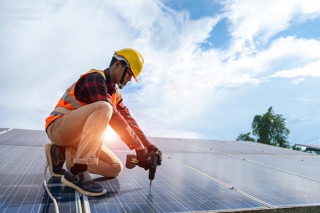 Техник по солнечным панелям с установкой сверл и обслуживанием солнечных панелей на крыше на солнечной электростанции, солнечной панели, альтернативного источника электроэнергии.