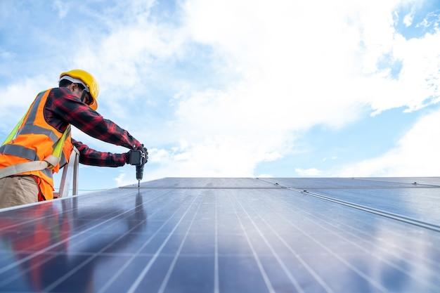Техник по солнечным батареям с дрелью, устанавливающий солнечные панели на крыше на поле солнечных батарей, охрана окружающей среды, концепция альтернативной чистой зеленой энергии.