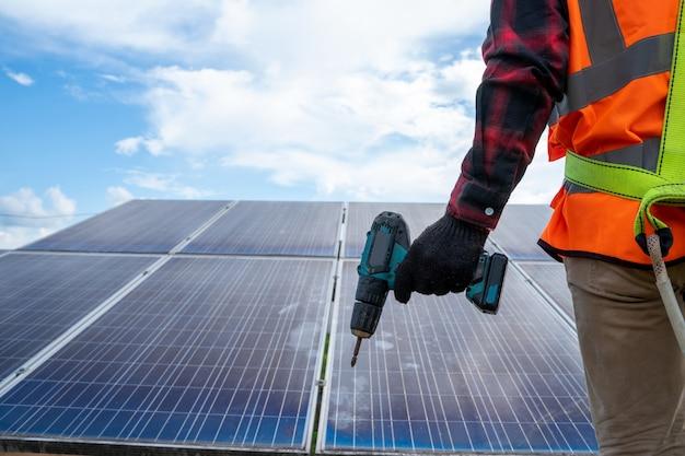 태양 전지 패널 분야의 지붕에 태양 전지 패널을 설치하는 드릴이 있는 태양 전지 패널 기술자, 환경 보호, 대체 청정 녹색 에너지 개념.