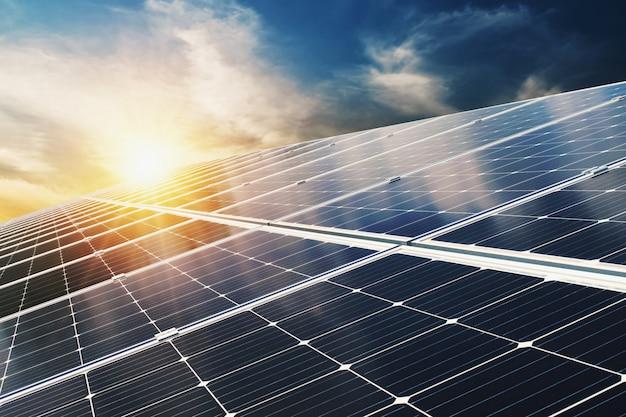 青い空と夕日と太陽電池パネル。コンセプトクリーンエネルギー、電気の代替、自然の力