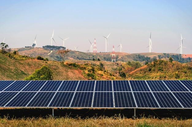 언덕과 푸른 하늘 배경에 터빈과 태양 전지 패널. 개념 청정 전력 에너지