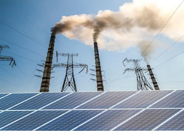 Solar panels against fuel coal power plant. sustainable development and renewable resources concept.