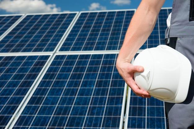흰색 보호 헬멧을 들고 태양 전지 패널 엔지니어