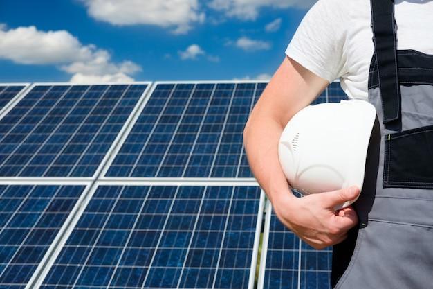 Solar panels engineer holding white protective helmet
