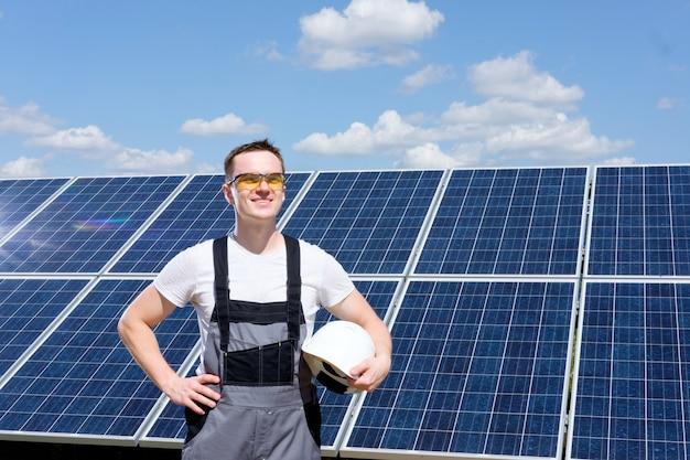 Инженер по солнечным батареям в желтых защитных очках и сером комбинезоне стоит возле поля солнечных батарей и держит белую бочку